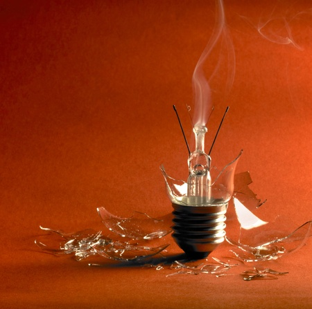 shards: broken upright light bulb with smoke and lots of shards in orange red back