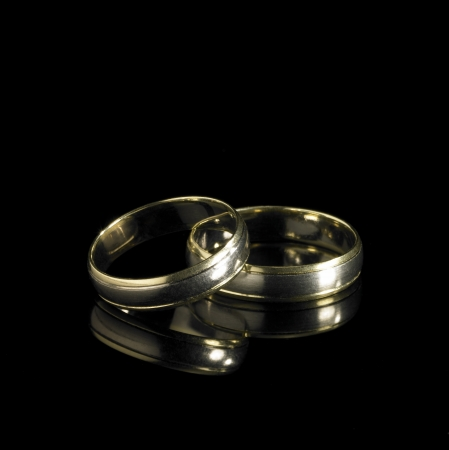 studio photography of 2 golden wedding rings in black reflective back photo