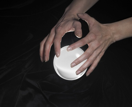 high angle shot of a glowing crystal ball surrounded by black crinkly fabrics and two hands around Stock Photo - 10839923
