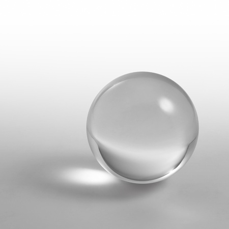 refraction of light: a clear crystal ball and light reflections in grey gradient back Stock Photo