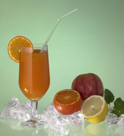 studio photography showing a glass of fruit juice with drinking straw, located in green ambiance with some fruits and ice cubes Stock Photo - 10839598