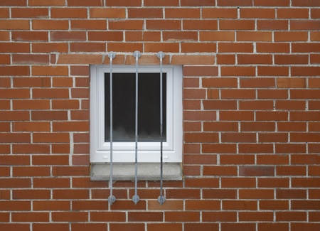 architectural detail of a barred window in a red brick wall photo
