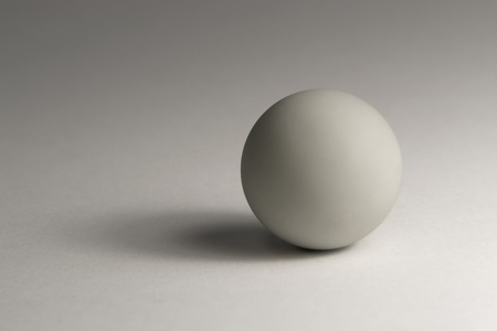 allegory painting: studio photography of a grey ball in light back