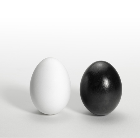 out of context: symbolic theme showing a black and a white egg upright side by side in light back Stock Photo