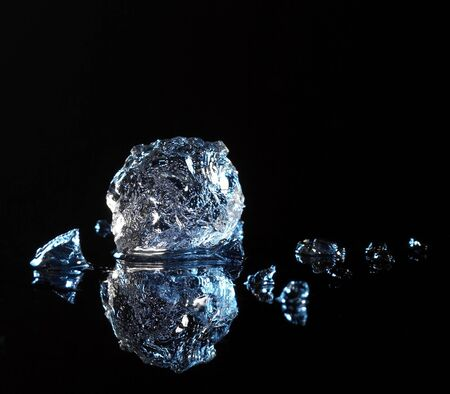 ice crushed: studio fotografie van een ijskristal en rook in het zwart reflecterende terug