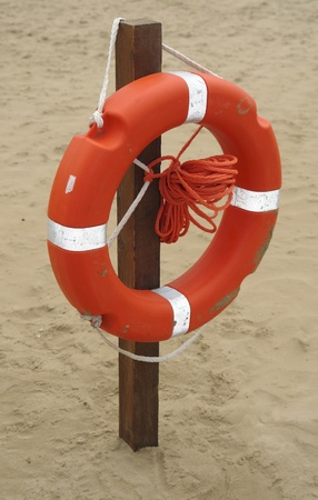 white-striped red life belt hanging on a stack at the beach photo