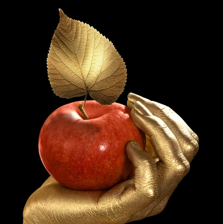 red apples: golden feminine hand holding a perfect red apple with golden leaf,Studio shot in black back