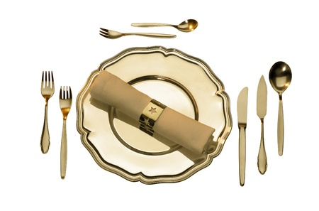 studio photography of a golden place setting in white back, seen from above