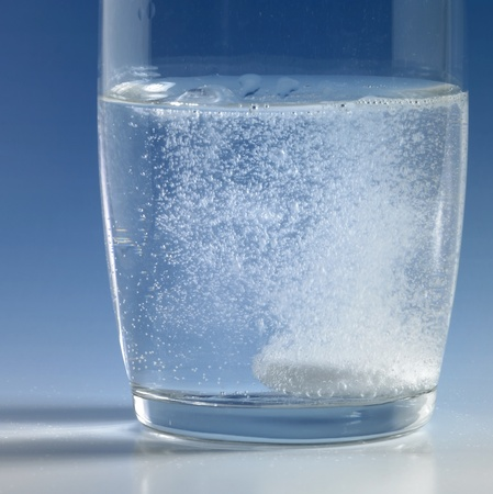 dissolving fizzy tablet floating in a glass of water. Studio photography in blue back Stock Photo - 10967326