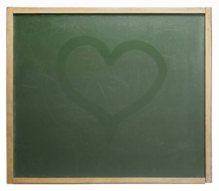 home schooling: old used blackboard with discreet wet painted heart shape on it. Studio photography in white back Stock Photo