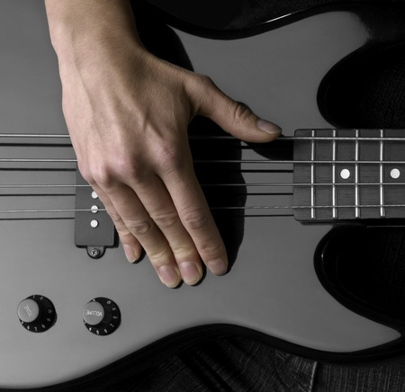 fretboard: female hand on the detail of a black bass guitar in dark back