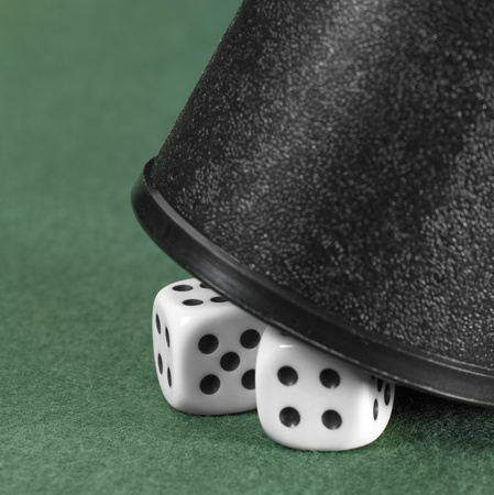 symbolic gambling background showing two dice under a half opened dice cup on green felt background photo