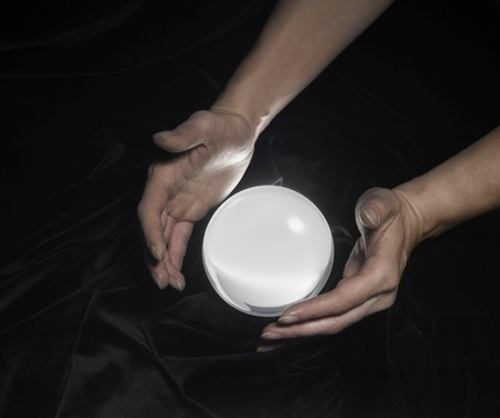 high angle shot of a glowing crystal ball surrounded by black crinkly fabrics and two hands around Stock Photo - 10862585