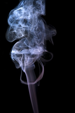 particulates: abstract picture showing some pastel colored smoke in black back Stock Photo
