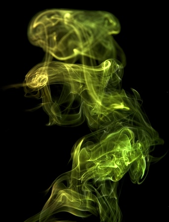 particulates: abstract picture showing some vibrant yellow and green colored smoke in black back Stock Photo