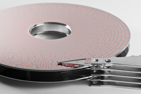 fixed disk: detail shot of a separated hard disk platter with actuator arm in light grey backAllegory theme regarding operation systems Stock Photo