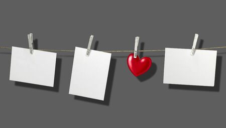 clothesline with some white labels and heart-shape fixed with clothes pins in front of grey back with shadow photo