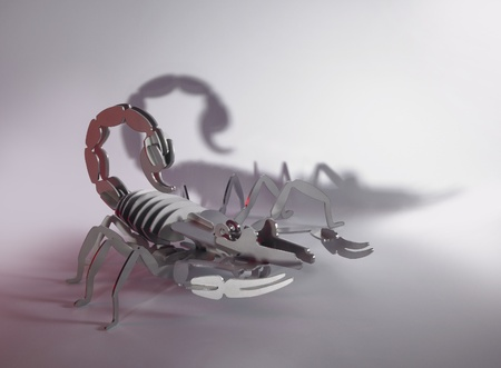 simplified scorpion made of metal, red illuminated photo