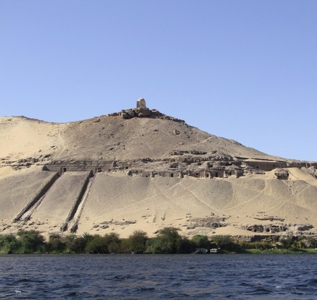 riparian: sunny scenery showing a ancient mausoleum on mountain top near Aswan in Egypt