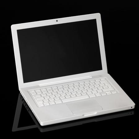 studio shot of a white Apple laptop in black reflective back photo