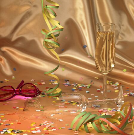 carnival background with a filled and a broken champagne glass in floating satin back with streamers and confetti photo