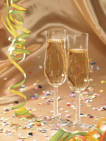 carnival scenery with filled stemware glasses and accessories in floating fabrics back with streamers and confetti photo