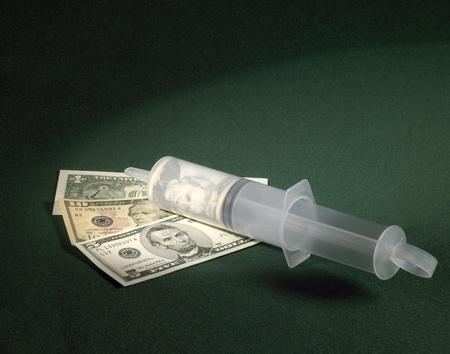 symbolic banking crisis theme showing a big plastic syringe and dollar banknotes on green felt photo