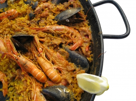 detail of a spanish dish named Paella in white back photo