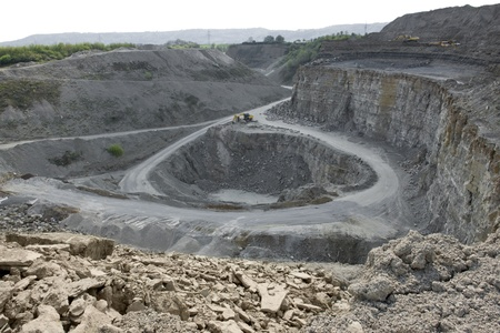yellow stone pit diggers and dump trucks in stony ambiance photo