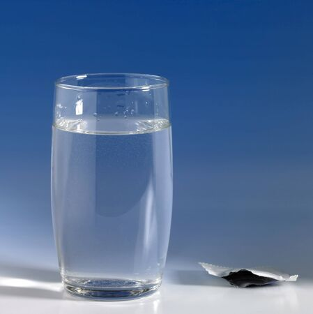 fizzy tablet: fizzy tablet solved in a glass of water, the empty casing beside. Studio shot in blue back Stock Photo