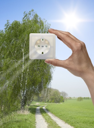 symbolic solar energy theme showing a idyllic outdoor scenery with human hand holding a electrical socket in front of the sun while sunbeams falling through photo