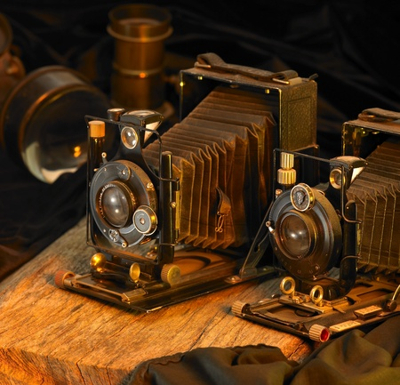 Still life with two nostalgic cameras and some accessories.Studio shot in warm toned ambiance