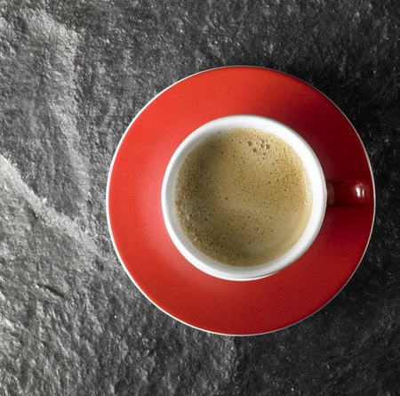 cup of coffee with crema, seen from above with red saucer on dark stone surface photo