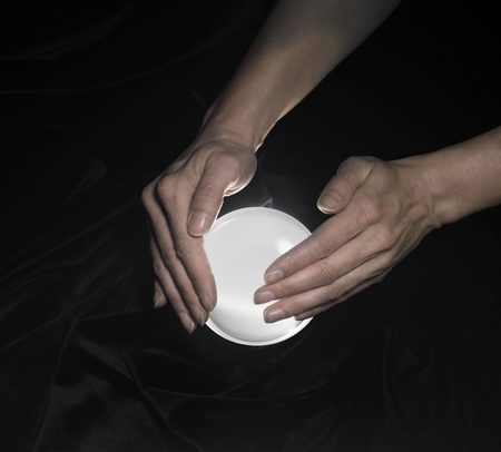 magical equipment: high angle shot of a glowing crystal ball surrounded by black crinkly fabrics and two hands around
