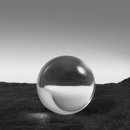 concealment: a clear crystal ball on rough dark grey stone surface in front of red back