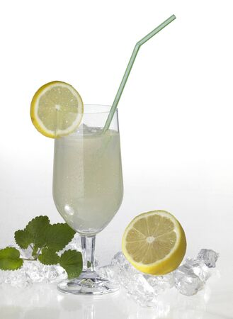 commercialization: studio photography of a translucent soft drink with sliced lemon and drinking straw in light back with lemon fruits and ice cubes