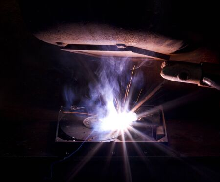 fusing: welding scenery with hard disk drive, welding mask detail and flashy light Stock Photo