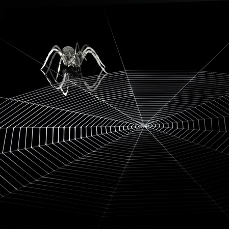 spider web: a simplified spider made of metal and a artificial spiderweb. Red illuminated studio shot in black back Stock Photo