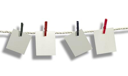 fixed: tendedero con algunas etiquetas de color gris claro fija con ganchos de ropa delante de fondo blanco con la sombra