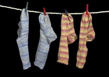 accouterment: clothesline with some multicolored sox fixed with clothes pins in black back