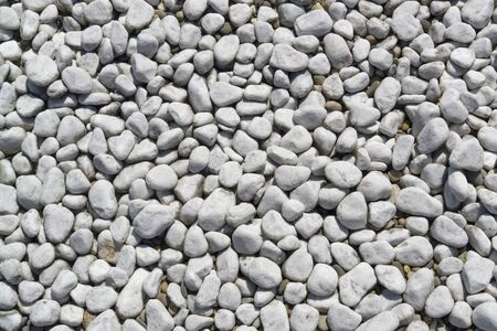 full frame abstract pebbles background in sunny ambiance, seen from above photo