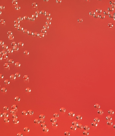 studio photography showing a heart shaped arrangement of clear drops in red back