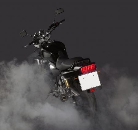 burnout: Detail von einem Motorrad und viel Rauch in dunklen Hinterzimmern Lizenzfreie Bilder
