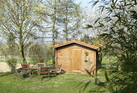 idyllic summerhouse and garden furniture at spring time