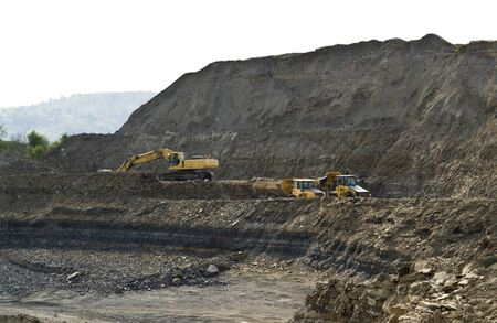 yellow stone pit digger and dump trucks in quarry ambiance photo