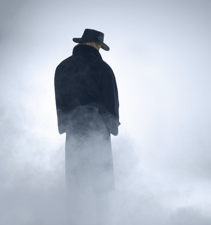 reclusion: woman with dark coat standing in the fog