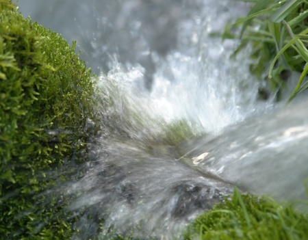 fount: freshnes theme with detail of a fount with splashing water and moss Stock Photo