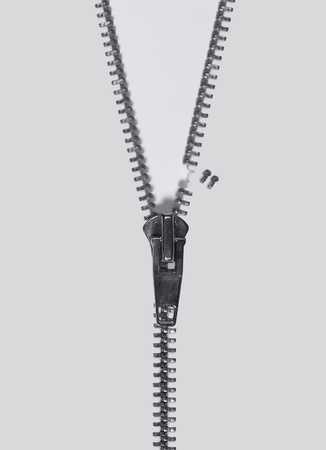 reachability: symbolic studio photography of a damaged zipper in light back, seen from above