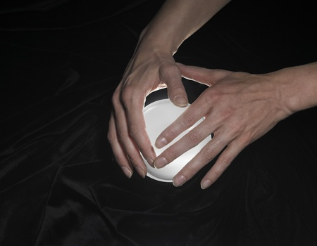 high angle shot of a glowing crystal ball surrounded by black crinkly fabrics and two hands around Stock Photo - 10917272