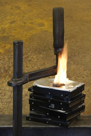 mass storage: stack of hard disks pressed by a screw clamp, some fire around Stock Photo